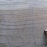 Draw the word onto the plank of wood using the pencil