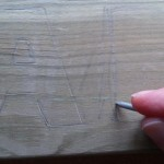 Score the word lightly onto the wood