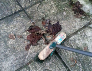 Brushing leaves and dirt from patio