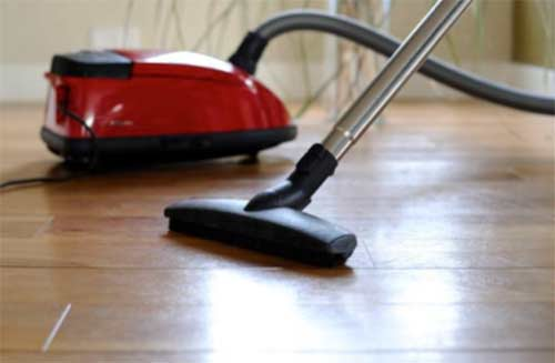 Vacuuming floor to remove dust