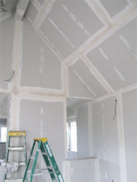 Drylining or plasterboarding walls