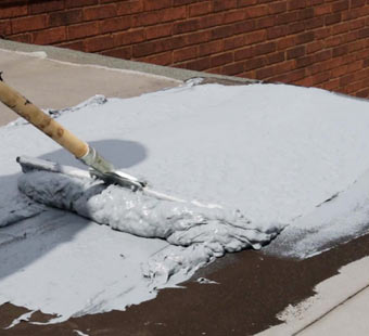 Using a squeegee to spread roof repair coating