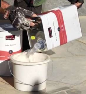 Pouring paving sealer into a paint kettle