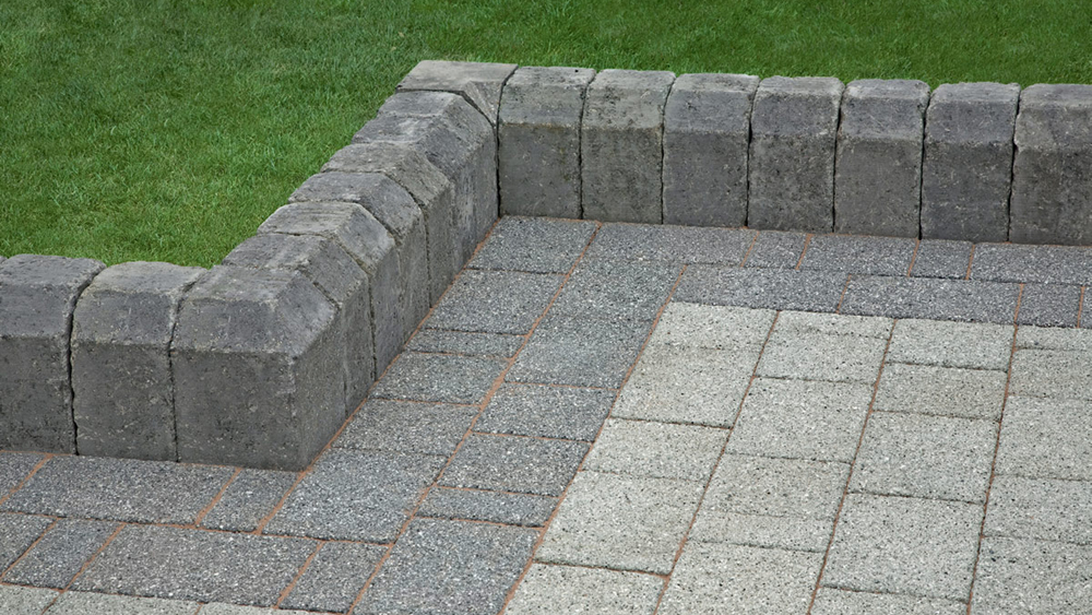 Laying Concrete Edging Stones Along A Driveway Or Pathway