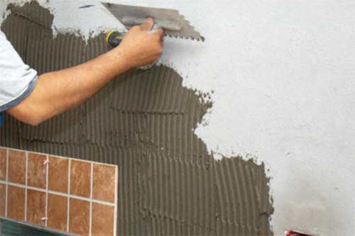 Applying adhesive to wall