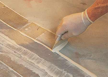 Applying floor tile adhesive