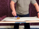 Applying wallpaper paste to a piece of wallpaper on a pasting table