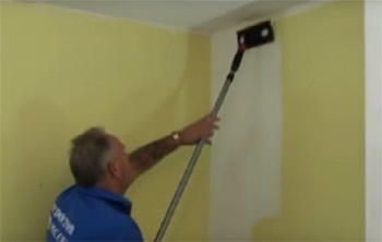 Using a paint pad to paint a wall