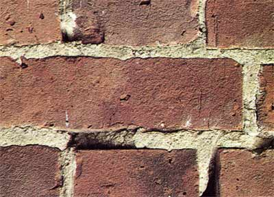 Old brickwork with broken and missing mortar in joints