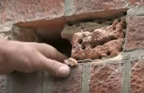 Brick in wall broken up with hammer and bolster