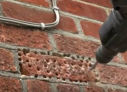 Brick drilled full of holes ready for breaking up