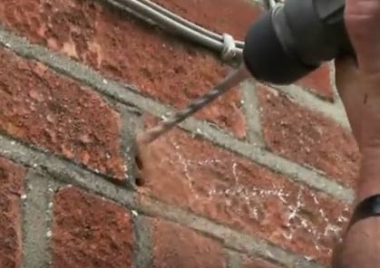 Drilling out old mortar to remove brick