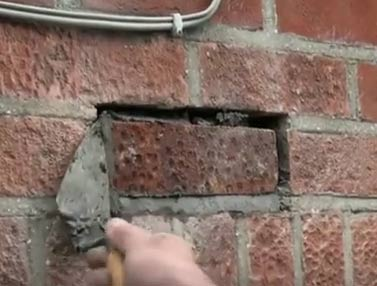 Forcing mortar into gaps around edge to fill holes