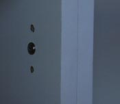 Screw behind door hinges