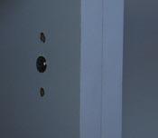 Screw behind door hinges