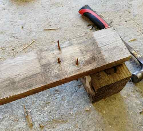 Knocking old nails back through pallet slats to remove them