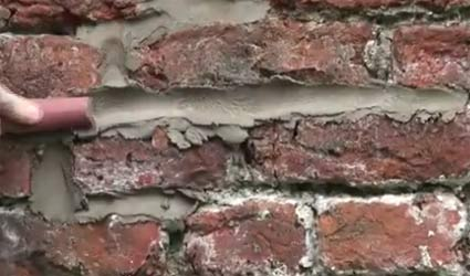 Pointing mortar joints with a piece of hosepipe