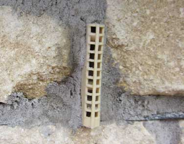 Plastic weephole vent inserted into brickwork joint