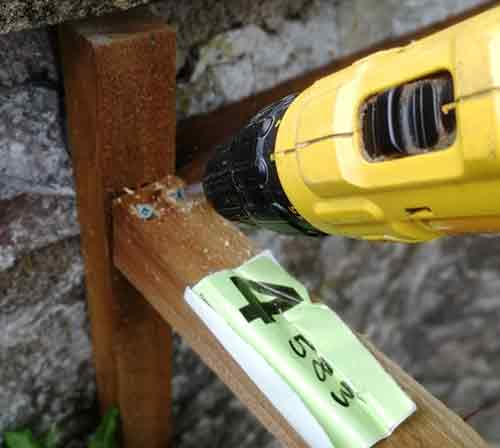 Screwing top timber in place between posts