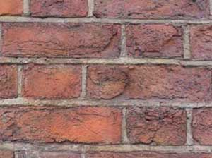 Brick wall showing faces have been blown off the bricks