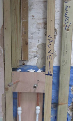 Concealed shower pipe tails sticking through false wall