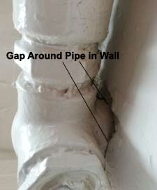 Gap around pipe penetrating internal cavity wall producing draughts and leaks