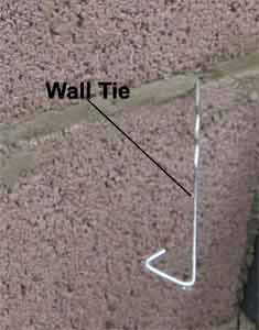 Wall tie fixed into wall course in internal cavity wall
