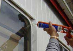 Using a silicone gun to waterproof windows and doors