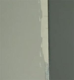 Applying first coat of filler to external corner