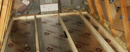 Insulation boards laid between joists