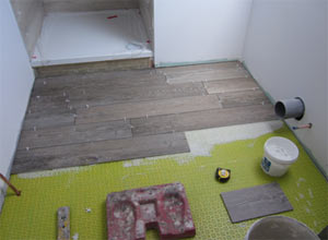 Wood grain effect Porcelain tiles laid in half bond brick pattern on a bathroom floor