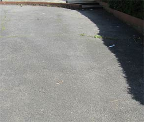 Aged tarmac driveway showing signs of cracking