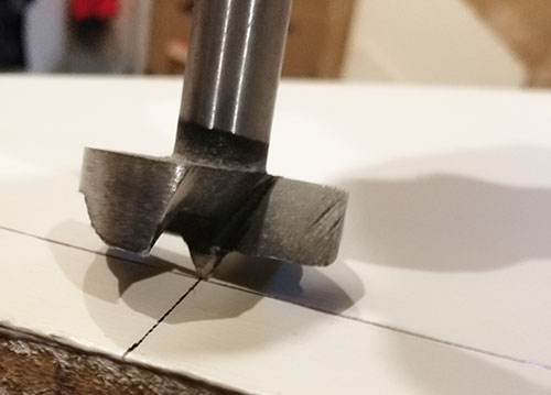 Forstner bit positioned at drilling point