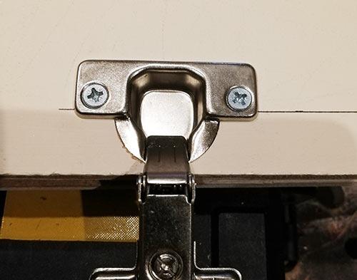 Concealed hinge screwed in place