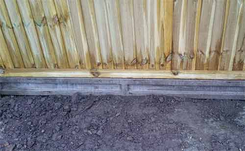 Concrete gravel board fitted to fence