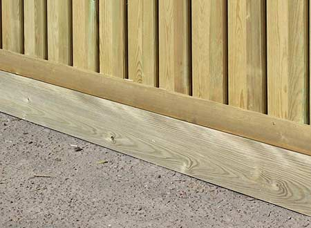 Timber gravel board fitted in place on a fence
