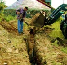 Trench containing ground source heating pipes being filled in