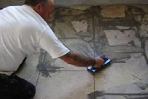 Using a grout float to spread tile grout into joints