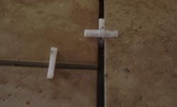 Tile spacers inserted into floor tiles leaving 5mm gap