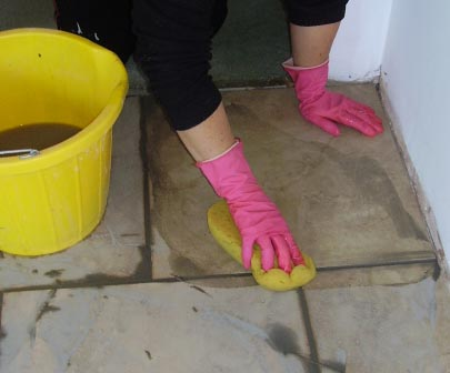 Using a sponge to wash off excess tile grout