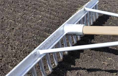 Raking over soil to prepare for laying turf