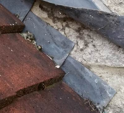 Apron flashing covers lead soakers on a plain tile roof
