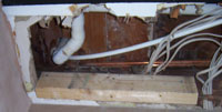 shower waste trap and pipework exposed through ceiling below