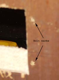 Close up of letter box bolt holes through door