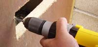 Using a cordless drill to drill letter box bolt holes