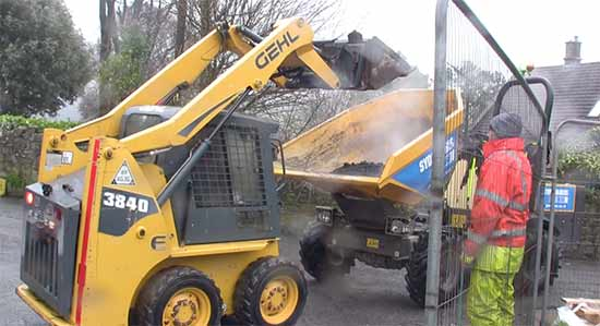 Loading bitmac from lorry into dumper using bobcat