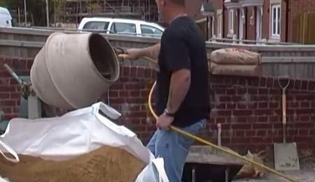 Using a hose to add water to cement mixer