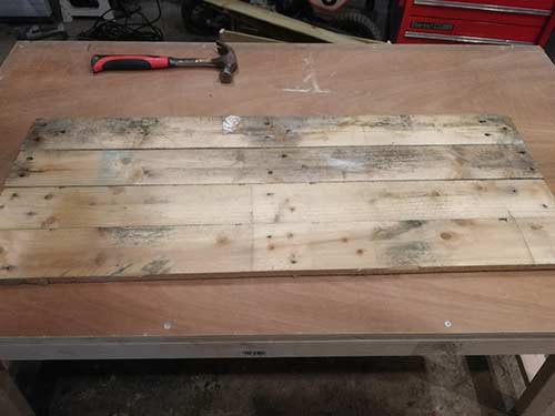 Pallet slats laid out and squared up to form chicken nesting box base