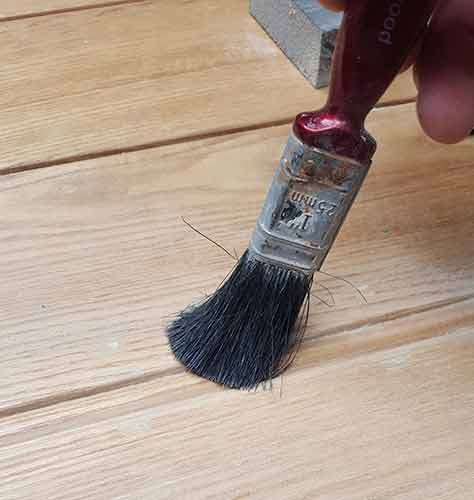 Using paint brush to clean dust from detail areas