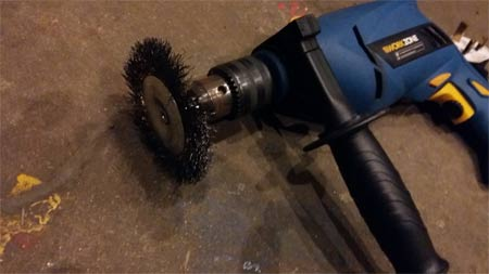 Power drill with wire brush attachment